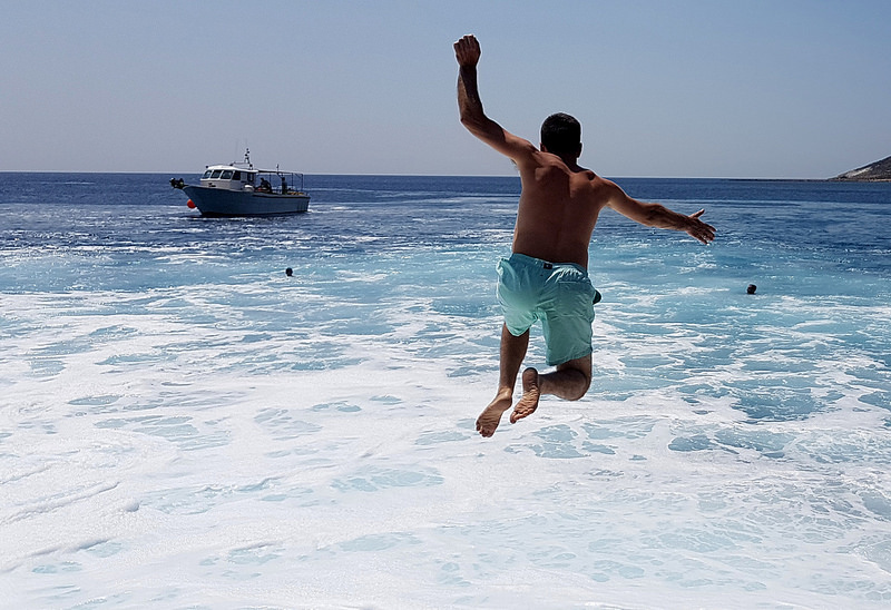 Boy jumping into the sea on Sikinos