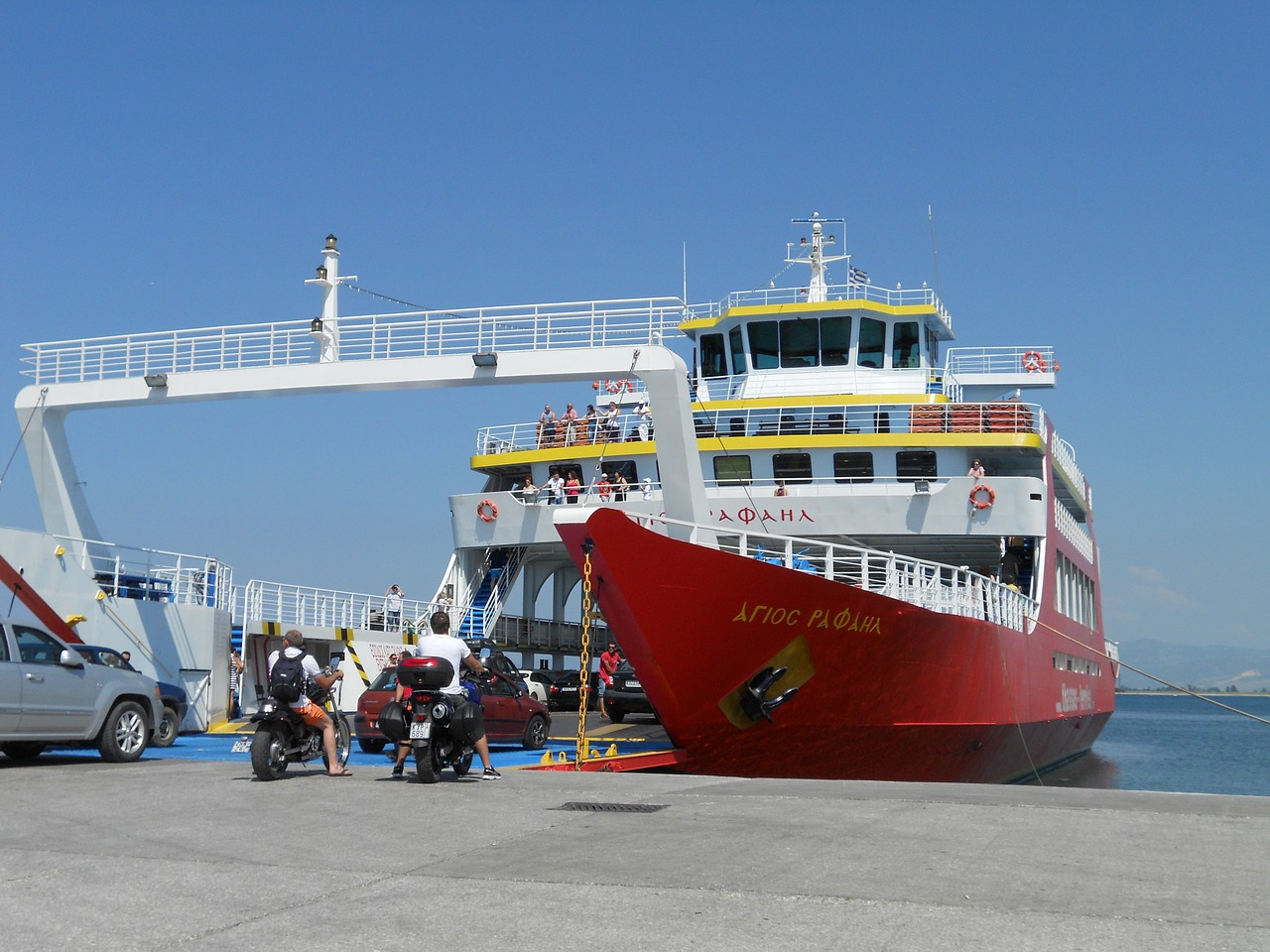 A red Greek ferry arriving at an island