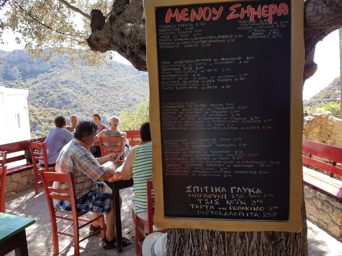 Blackboard and diners at Sto Scholeio Taverna in Anidri, Crete