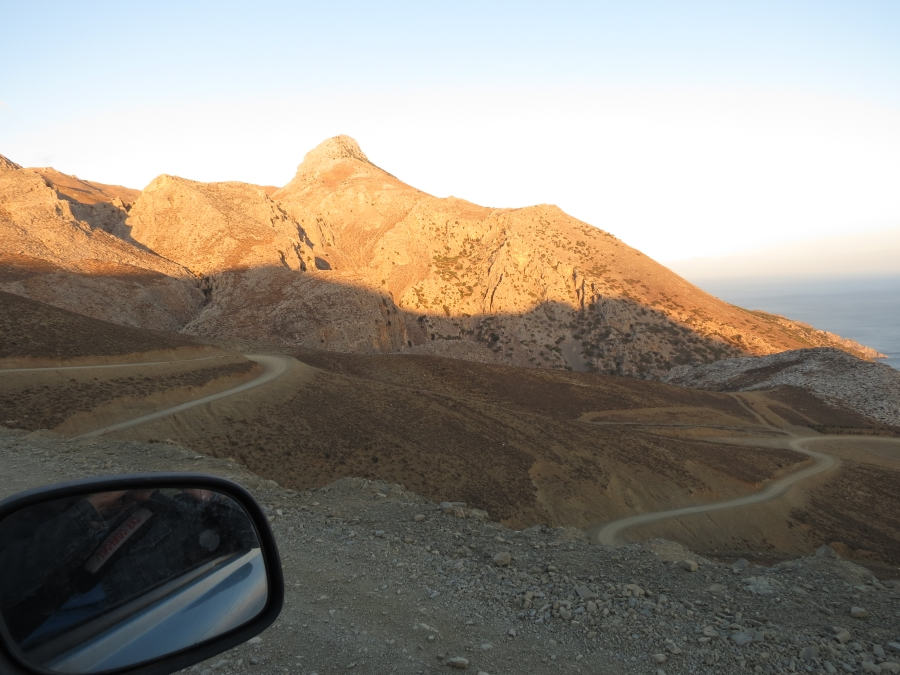 A rental car mirror and a winding road on Crete in Greece