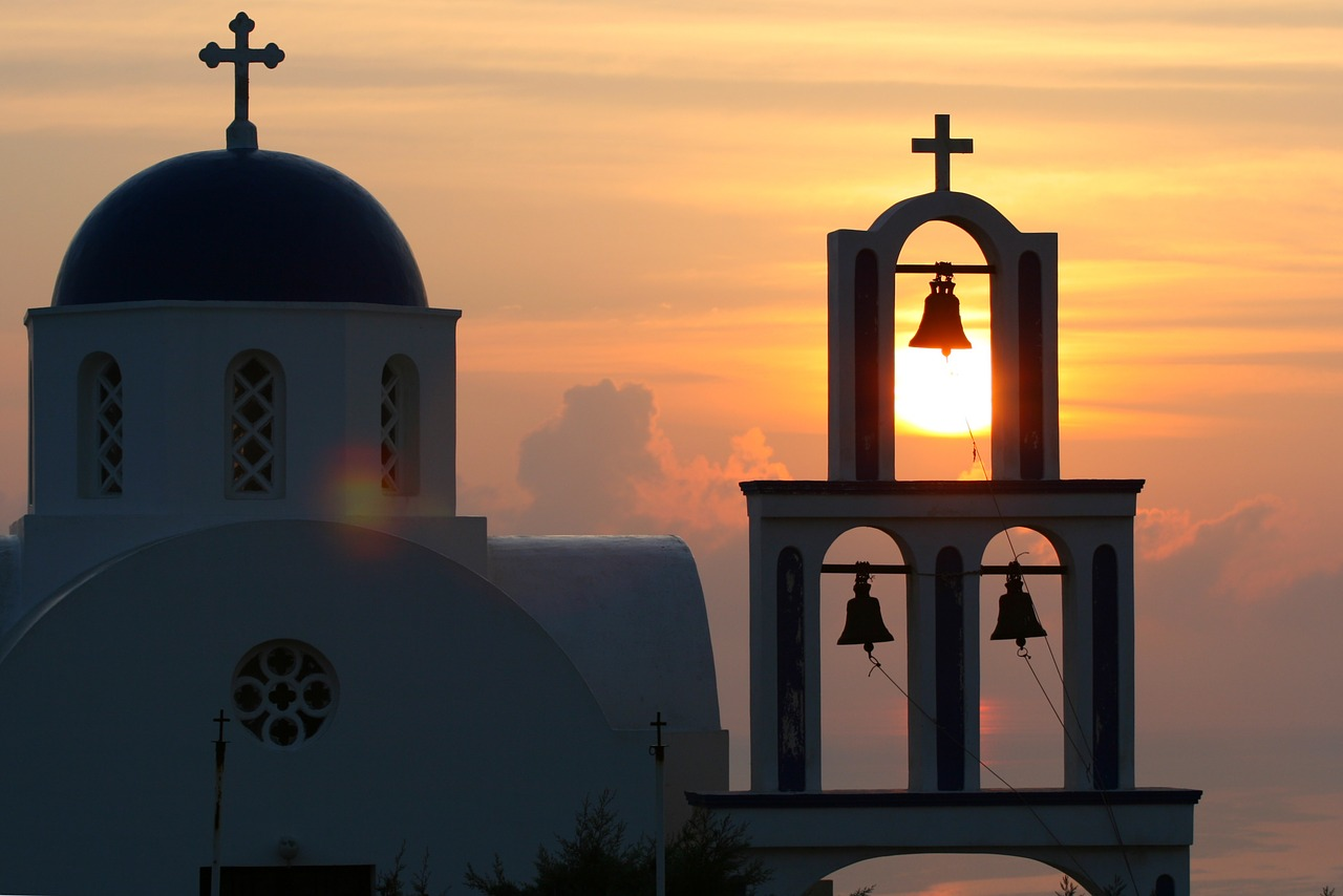 A church with bells at sunset on Santorini in the Cyclades Islands of Greece
